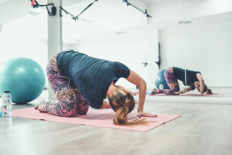 Female Athlete Doing Advanced Yoga Exercises In Gym