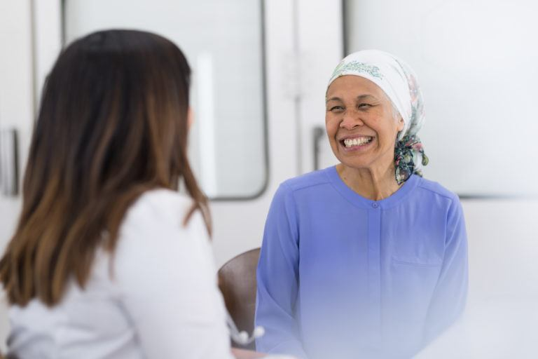 A senior woman battling cancer talks with her doctor at the hospital. She is wearing a headcovering and smiling. The shot is over the doctor's right shoulder.